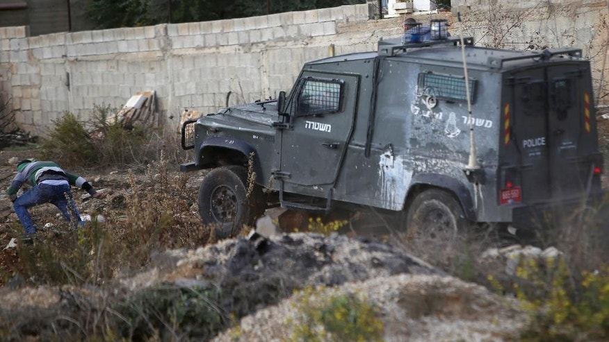 "In this Friday, Oct. 30, 2015 photograph, an Israeli police jeep charges towards a Palestinian demonstrator, who was hit by the jeep moments later, beaten and arrested during clashes outside Ramallah, West Bank. Recent video has shown Israeli troops shooting a Palestinian lying in a street from close range, pepper-spraying Palestinian medics, chasing and ramming a Palestinian with their jeep and threatening refugee camp residents with tear gas ""until you die"" unless they stop throwing stones. The flurry of such footage comes at a time when growing numbers of Palestinians for the first time have the tools to document such incidents; half of Palestinian households have at least one smart phone, or 10-fold what it was five years ago, according to official statistics. (AP Photo/Shadi Hatem)"