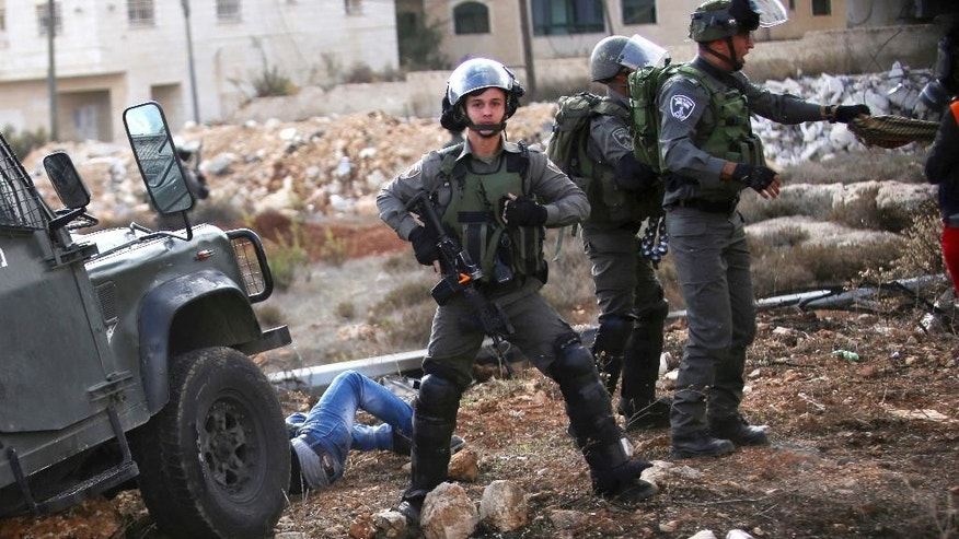 "In this Friday, Oct. 30, 2015 photo,  Israeli police stand guard after their jeep charged and hit a Palestinian demonstrator during clashes outside Ramallah, West Bank. Recent video has shown Israeli troops shooting a Palestinian lying in a street from close range, pepper-spraying Palestinian medics, chasing and ramming a Palestinian with their jeep and threatening refugee camp residents with tear gas ""until you die"" unless they stop throwing stones. The flurry of such footage comes at a time when growing numbers of Palestinians for the first time have the tools to document such incidents; half of Palestinian households have at least one smart phone, or 10-fold what it was five years ago, according to official statistics.(AP Photo/Shadi Hatem)"