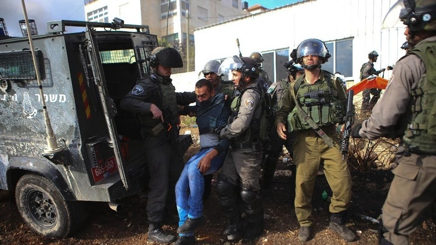 "In this Friday, Oct. 30, 2015 photograph, Israeli border police arrests a Palestinian demonstrator, who was hit by their jeep during clashes outside Ramallah, West Bank. Recent video has shown Israeli troops shooting a Palestinian lying in a street from close range, pepper-spraying Palestinian medics, chasing and ramming a Palestinian with their jeep and threatening refugee camp residents with tear gas ""until you die"" unless they stop throwing stones. The flurry of such footage comes at a time when growing numbers of Palestinians for the first time have the tools to document such incidents; half of Palestinian households have at least one smart phone, or 10-fold what it was five years ago, according to official statistics.(AP Photo/Shadi Hatem)"