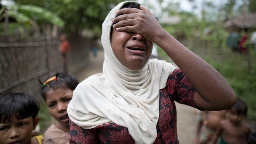 In this Oct. 13, 2015 photo, Salema Khatu reacts after seeing a photograph taken of her son, Habil, months before he died from complications related to tuberculosis in an area for Muslim refugees in north of Sittwe, western Rakhine state, Myanmar. Like other Rohingya Muslims living in Western Myanmar, the 10-year-old was unable to get proper medical treatment. As the predominantly Buddhist nation of 50 million started transitioning from dictatorship toward democracy in 2011, the rise in radical Buddhist nationalism has taking advantage of the newfound freedoms of expression to fan prejudices against the long-persecuted Rohingya Muslim minority. Hate-filled sermons have helped incite violence that began in 2012, leaving hundreds dead and sending a quarter-million others fleeing their homes. (AP Photo/Gemunu Amarasinghe)