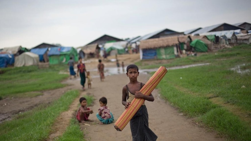 In this June 24, 2014 photo, a Rohingya boy walks with a mat as children play in the background at Dar Paing camp for Muslim refugees in north of Sittwe, western Rakhine State, Myanmar. As the predominantly Buddhist nation of 50 million started transitioning from dictatorship toward democracy in 2011, the rise in radical Buddhist nationalism has taking advantage of the newfound freedoms of expression to fan prejudices against the long-persecuted Rohingya Muslim minority. Hate-filled sermons have helped incite violence that began in 2012, leaving hundreds dead and sending a quarter-million others fleeing their homes. (AP Photo/Gemunu Amarasinghe)