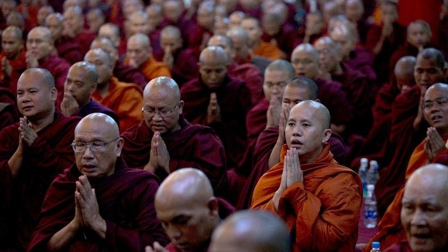 In this June 27, 2013 photo, controversial Buddhist monk Wirathu, second right foreground, who is accused of instigating sectarian violence between Buddhists and Muslims through his sermons, performs Buddhist rituals with Myanmar's powerful Buddhist clergy in outskirts of Yangon, Myanmar. As the predominantly Buddhist nation of 50 million started transitioning from dictatorship toward democracy in 2011, the rise in radical Buddhist nationalism has taking advantage of the newfound freedoms of expression to fan prejudices against the long-persecuted Rohingya Muslim minority. Hate-filled sermons have helped incite violence that began in 2012, leaving hundreds dead and sending a quarter-million others fleeing their homes. (AP Photo/Gemunu Amarasinghe)