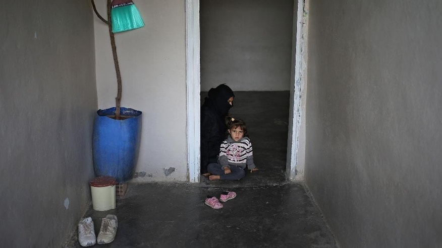 In this picture taken on Friday Oct. 23, 2015, Syrian refugee Hind Salem, 31, who fled with her family from the central Syrian town of Palmyra, from Russian airstrikes, sits on the ground with her daughter Yara, 3, at their unfurnished home, in the Turkish-Syrian border city of Reyhanli, southern Turkey. Activists say most Russian strikes have targeted Syrian rebels not connected to IS, including U.S.-backed factions, with the aim of weakening them and tipping the conflict in favor of Moscow's ally, President Bashar Assad. (AP Photo/Hussein Malla)