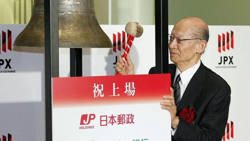 Taizo Nishimuro, president of Japan Post Holdings, rings the bell during a ceremony at the Tokyo Stock Exchange in Tokyo Wednesday, Nov. 4, 2015. Shares of Japan Post jumped nearly 17 percent in the first day of trading after the company and its banking and insurance units raised a combined 1.44 trillion yen ($11.9 billion) in the world's biggest initial public offering of stock this year. (Kyodo News via AP) JAPAN OUT, MANDATORY CREDIT
