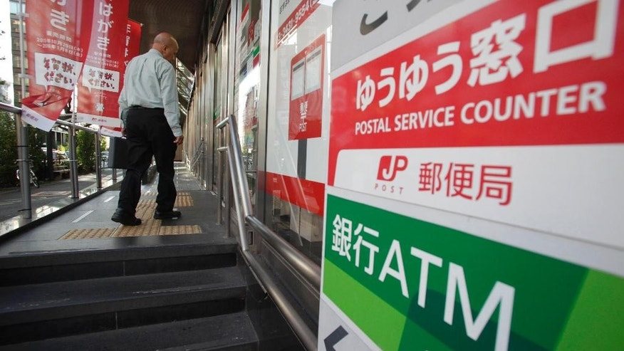 A man enters a post office in Tokyo, Wednesday, Nov. 4, 2015. Shares of Japan Post surged nearly 26 percent in their trading debut Wednesday after the company and its banking and insurance units raised a combined 1.44 trillion yen ($11.9 billion) in the world's biggest initial public offering this year. (AP Photo/Shizuo Kambayashi)