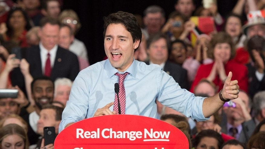 FILE - In this Oct. 20, 2015, file photo, Prime minister designate Justin Trudeau speaks to supporters at a rally in Ottawa, Ontario. Trudeau will be sworn in Wednesday, Nov. 4 as prime minister, the position long held by his late father, as Canada begins a new era of Liberal leadership after Conservative Stephen Harper's near-decade in power. (Adrian Wyld/The Canadian Press via AP, File) MANDATORY CREDIT