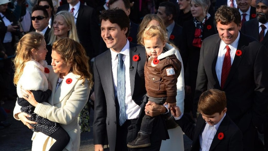 Prime Minister-designate Justin Trudeau, his wife Sophie Gregoire-Trudeau and their children Ella-Grace, Hadrien and Xavier lead the new Liberal cabinet to Rideau Hall in Ottawa on Wednesday, Nov. 4, 2015.  Trudeau has been sworn in as Canada's next prime minister, following in the footsteps of his storied father.  (Sean Kilpatrick/The Canadian Press via AP) MANDATORY CREDIT
