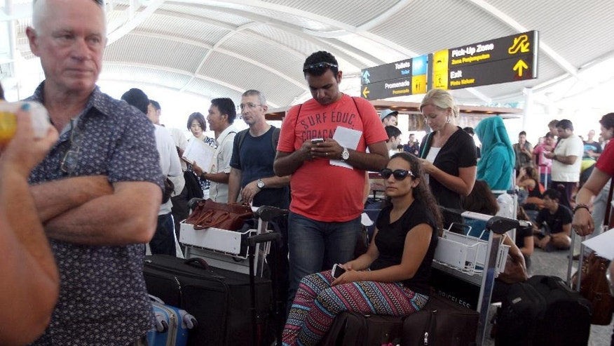 Passengers wait to check the status of their flights with airline desk at Ngurah Rai International Airport in Bali, Indonesia Wednesday, Nov. 4, 2015. Ash spewing from a rumbling volcano in eastern Indonesia blanketing villages with thick ash, forcing the closure of two airports and international airlines canceled flights to tourist hotspot Bali, stranding thousands. (AP Photo/Firdia Lisnawati)