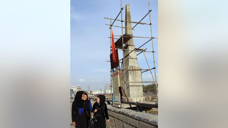 Afghan young ladies walk past an unfinished monument dedicated to Farkhunda who was beaten to death by a mob in March 2015 after being falsely accused of burning a Quran, in Kabul, Afghanistan, Wednesday, Nov. 4, 2015. A 22-year-old Afghan woman was thrown in a hole in the ground and stoned to death by a group of men identified as Taliban insurgents after she was accused of adultery, an Afghan official said on Wednesday. (AP Photos/Rahmat Gul)
