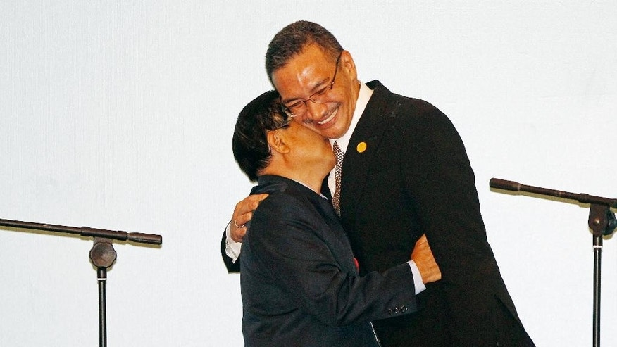 Malaysia's Defense Minister Hishamuddin Hussein, right, embraces with Laos' Defense Minister Sengnouane Sayalat during the hand over ceremony of the Association of Southeast Asian Nations (ASEAN) Defense Ministers' Meeting Chairmanship after the ASEAN Defense Ministers' Meeting Plus in Kuala Lumpur, Malaysia, Wednesday, Nov. 4, 2015. (AP Photo/Lai Seng Sin)
