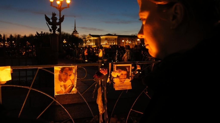 A woman stands in front of pictures of the plane crash victims are attached to the fence at Dvortsovaya (Palace) Square in St.Petersburg, Russia, Tuesday, Nov. 3, 2015. Mourners continued to come to St. Petersburg's Pulkovo airport and Dvortsovaya Square on Tuesday to lay flowers and leave paper planes and soft toys at the arrivals hall. (AP Photo/Dmitry Lovetsky)