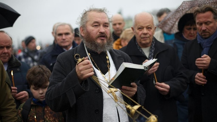 An Orthodox priest conducts an improvised religious service in memory of the plane crash victims in St. Petersburg, Russia, on Wednesday, Nov. 4, 2015. A Russian official says families have identified the bodies of 33 victims killed in Saturday's plane crash over Egypt. The Russian jet crashed over the Sinai Peninsula early Saturday, killing all 224 people on board, most of them were holidaymakers. (AP Photo/Ivan Sekretarev)