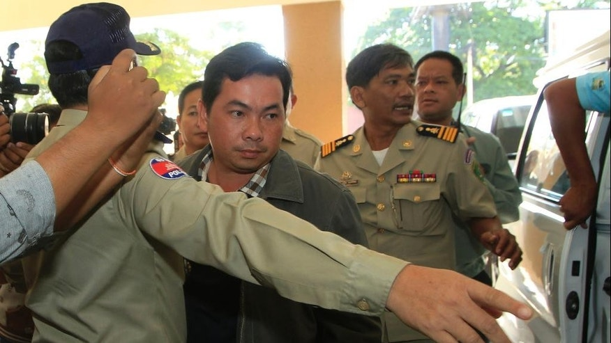 Chay Sarith, center, a suspected attacker who is accused of beating two opposition lawmakers along with two others, is escorted by police officers at Phnom Penh Municipal Court in Phnom Penh, Cambodia, Wednesday, Nov. 4, 2015. Three suspects of the assault outside of the National Assembly last week made confessions on Tuesday, according to a government statement released late Tuesday. (AP Photo/Heng Sinith)