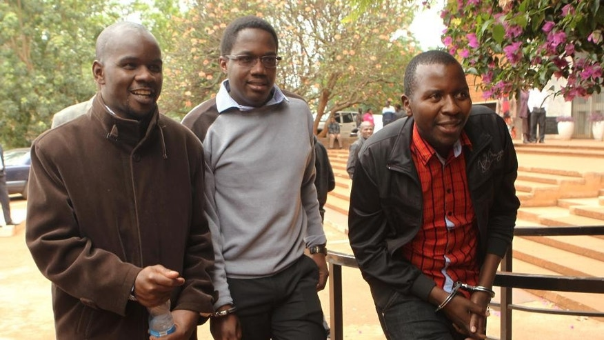 Zimbabwean journalists Brian Chitemba, left, Mabasa Sasa, centre, and Tinashe Farawo walk in handcuffs, outside the magistrates courts in Harare, Zimbabwe, Wednesday, Nov. 4.2015. A Zimbabwean court has granted bail to three journalists accused of slander after they allegedly implicated an unnamed top police officer and other officials in the fatal cyanide poisonings of more than 60 elephants by poachers. (AP Photo/Tsvangirayi Mukwazhi)