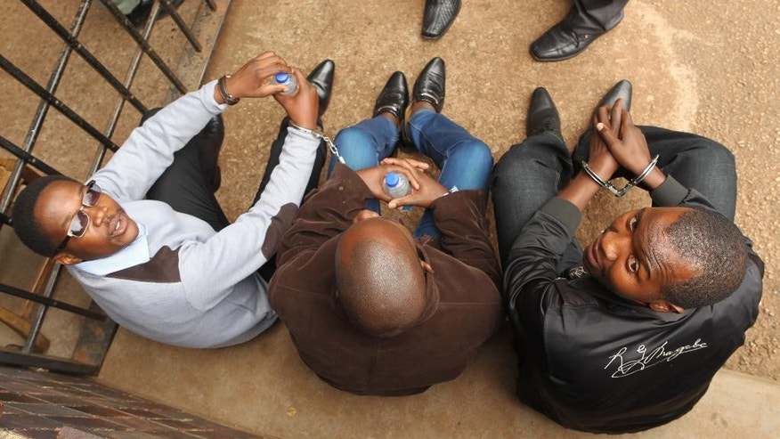 Zimbabwean journalists, Mabasa Sasa, left, Brian Chitemba, centre, and Tinashe Farawo sit handcuffed, after appearing at the magistrates courts in Harare, Zimbabwe, Wednesday, Nov. 4 2015. A Zimbabwean court has granted bail to three journalists accused of slander after they allegedly implicated an unnamed top police officer and other officials in the fatal cyanide poisonings of more than 60 elephants by poachers. (AP Photo/Tsvangirayi Mukwazhi)