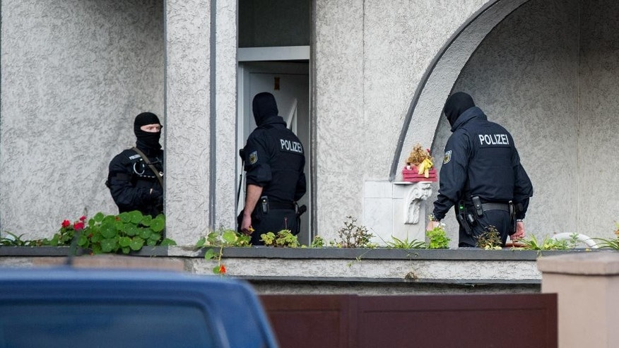 Masked police officers enter a house in Essen, Germany, Wednesday Nov. 4, 2015. Germany's federal police are conducting raids against international human trafficking networks across Germany. Hundreds of thousands of migrants have flooded to Germany in recent months seeking to escape war and poverty and start a new life. Many of them pay human smugglers to take them across the borders into the country.  (Marcel Kusch/dpa via AP)