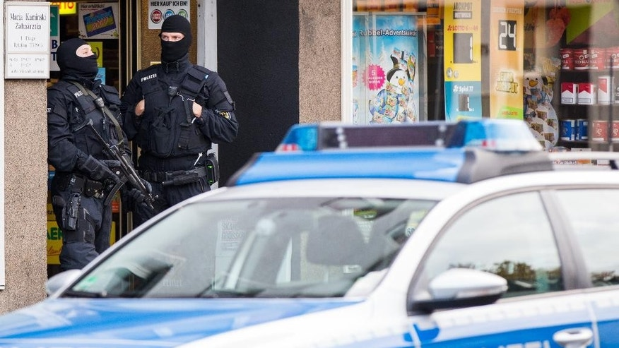 Masked police officers stand in front of a house in Essen, Germany, Wednesday Nov. 4, 2015.  Germany's federal police are conducting raids against international human trafficking networks across Germany. Hundreds of thousands of migrants have flooded to Germany in recent months seeking to escape war and poverty and start a new life. Many of them pay human smugglers to take them across the borders into the country.  (Marcel Kusch/dpa via AP)