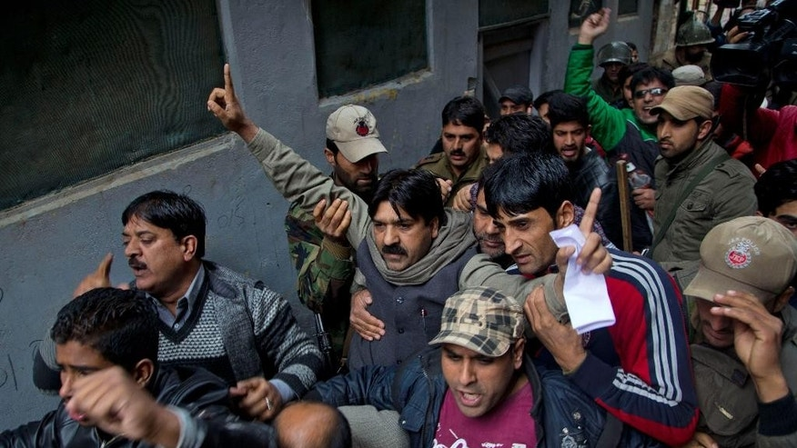 Kashmiris shout slogans after Indian police detained separatist People's Political Party (PPP) leader Hilal Ahmad War, center wearing a shawl around his neck, in Srinagar, Indian controlled Kashmir, Wednesday, Nov. 4, 2015. Indian authorities have detained key separatist leaders and hundreds of their supporters to prevent them from protesting during Prime Minister Narendra Modi's visit to Kashmir this weekend. (AP Photo/Dar Yasin)