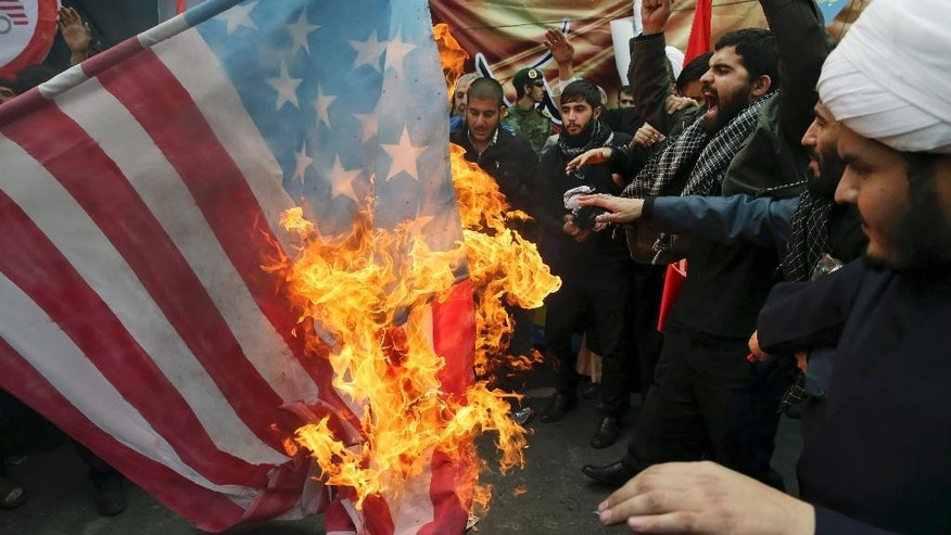 Iranian demonstrators burn a representation of the U.S. flag during an annual rally in front of the former U.S. Embassy in Tehran, marking 36th anniversary of the seizure of the embassy by militant Iranian students, Iran, Wednesday, Oct. 4, 2015. The annual state-organized rally Wednesday drawing greater attention this year, as Iranian hardliners are intensifying a campaign to undermine President Hassan Rouhani's outreach to the West following a landmark nuclear deal reached with world powers in July. (AP Photo/Vahid Salemi)