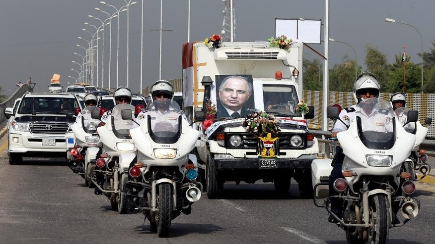 Security forces and mourners escort the coffin of Ahmad Chalabi, seen in the poster at center, during his funeral procession in Baghdad, Iraq, Wednesday, Nov. 4, 2015. Iraqi Prime Minister Haider al-Abadi and other senior Iraqi dignitaries are paying their final respects to Chalabi who died on Tuesday of a heart attack. The prominent Iraqi politician became a Pentagon favorite when he helped convince the Bush administration to overthrow Saddam Hussein in 2003 by pushing false allegations of weapons of mass destruction and links to al-Qaida. (AP Photo/Hadi Mizban)