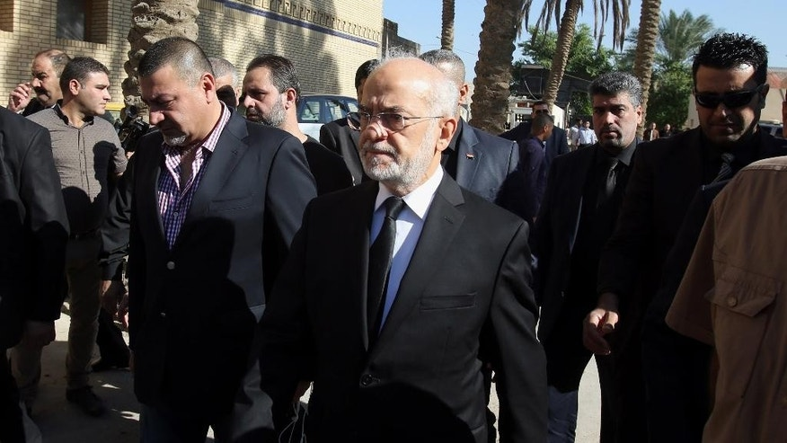 Iraqi Foreign Minister Ibrahim al-Jaafari, center, arrives to attend the funeral of Ahmad Chalabi, in Baghdad, Iraq, Tuesday, Nov. 3, 2015.  Chalabi, a prominent Iraqi politician who strongly advocated for the 2003 U.S.-led invasion to overthrow Saddam Hussein, has died of a heart attack, Iraqi state TV reported Tuesday. (AP Photo/Karim Kadim)