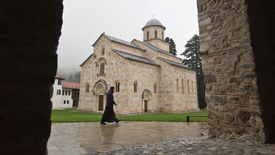 In this Tuesday, Oct. 20, 2015 photo, a monk walks past the Orthodox monastery of Visoki Decani placed on UNESCO's World Heritage List under the name of Medieval Monuments in Kosovo. One of the key selling points of Kosovo's bid is its promise to protect the cultural heritage of Serbs. It's a complicated issue because ethnic Albanian guerrillas fought the Serb army in their 1998-1999 war of independence. (AP Photo/Visar Kryeziu)