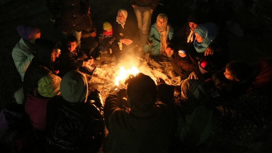 In this Nov. 3, 2015 photo migrants sit around a campfire after crossing the border between Slovenian and Austria in Spielfeld, Austria. Tens of thousands of people are trying to reach central and northern Europe via the Balkans but often have to wait for days in mud and rain at the Serbian, Croatian and Slovenian borders. (AP Photo/Ronald Zak)