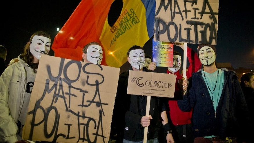 "Protesters wearing masks hold banners that read: ""Down the Political Mafia"" during a rally calling for early elections, joined by thousands in University Square in Bucharest, Romania, Wednesday, Nov. 4, 2015. Prime Minister Victor Ponta announced the resignation of his government Wednesday following huge protests the day before in the wake of a nightclub fire that killed more than 30 people. (AP Photo/Vadim Ghirda)"