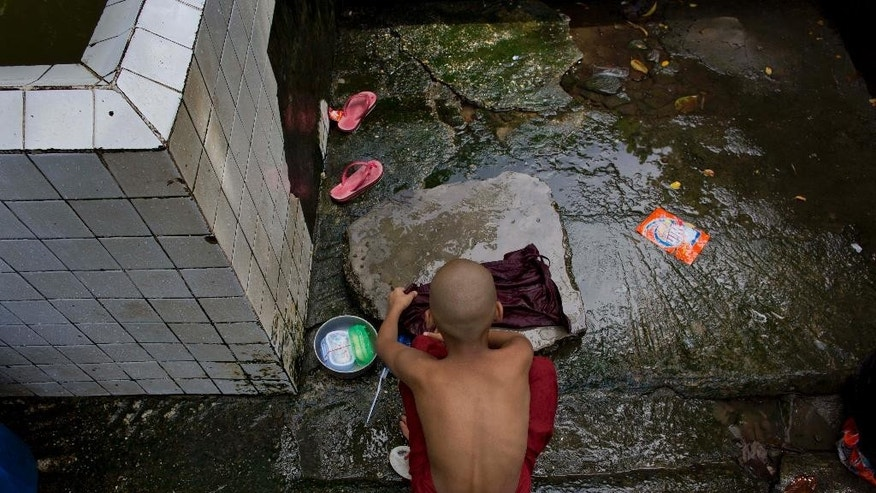 In this June 12, 2015 photo, a novice Buddhist monk washes his robes at Bahan Thone Htat monastic school in Yangon, Myanmar. Monasteries in Yangon have retained their traditional role as providers of education and even health care. (AP Photo/Gemunu Amarasinghe)