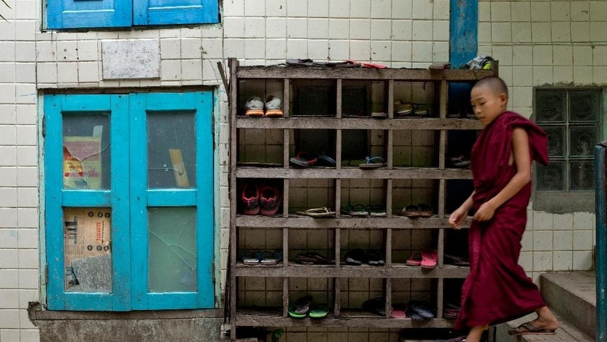 In this June 12, 2015 photo, a novice Buddhist monk walks down steps passing a footwear stand at Bahan Thone Htat monastic school in Yangon, Myanmar. Monasteries have retained their traditional role as providers of education and even health care in Yangon. (AP Photo/Gemunu Amarasinghe)