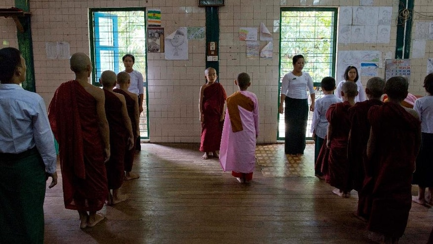 In this June 12, 2015 photo, novice Buddhist monks, nuns, children and teachers sing Myanmar's National anthem during an assembly at the beginning of a school day at Bahan Thone Htat monastic school in Yangon, Myanmar. As a bell rings, novice Buddhist monks and nuns in their saffron and pink robes, and other children in crisp white shirts, file barefoot up the stairs to line up for their morning assembly at the monastic school.  (AP Photo/Gemunu Amarasinghe)