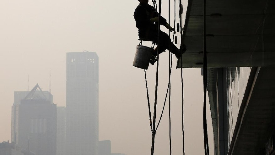A worker is silhouetted as he cleans a window at a shopping mall in Beijing, China, Wednesday, Nov. 4, 2015. President Xi Jinping said on Tuesday that China needs at least 6.5 percent economic growth in coming years and the Communist Party announced plans to let its tightly controlled yuan trade freely by 2020.  (AP Photo/Andy Wong)