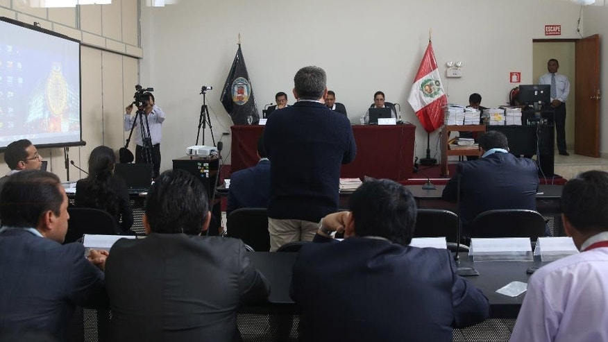 In this Oct. 29, 2015 photo, former chief of the Presidential Commission of Presidential pardons, Miguel Facundo Chinguel, back to camera, speaks during his trial at the Piedras Gordas prison in Ancon, Peru. Prosecutors allege that during the presidency of Alan Garcia, Facundo is one of many subordinates who approached inmates who could pay to get out of jail. He's now the lead defendant in the narco pardon case, but insists he's innocent, including of the accusation that he personally received money in exchange for securing the release of a convicted Colombian trafficker, Ramiro Castro Mendoza, in 2009. (AP Photo/Martin Mejia)