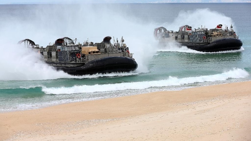 FILE - In this Oct. 20, 2015, file photo, U,S, Navy hovercrafts approach the beach at the beginning of the NATO Trident Juncture exercise 2015 at Raposa Media beach in Pinheiro da Cruz, south of Lisbon. NATO is putting on its most fearsome display of military might in over a decade, a choreographed exercise of soldiers, ships and planes, all meant to hone and test its current abilities. (AP Photo/Steven Governo, File)