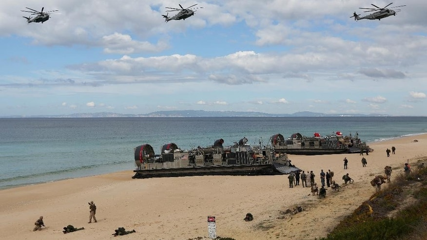FILE - In this Oct. 20, 2015 file photo, U.S. navy helicopters fly over U.S. Navy hovercraft during the NATO Trident Juncture exercise 2015 at Raposa Media beach in Pinheiro da Cruz, south of Lisbon. NATO is putting on its most fearsome display of military might in over a decade, a choreographed exercise of soldiers, ships and planes, all meant to hone and test its current abilities. (AP Photo/Steven Governo, File)