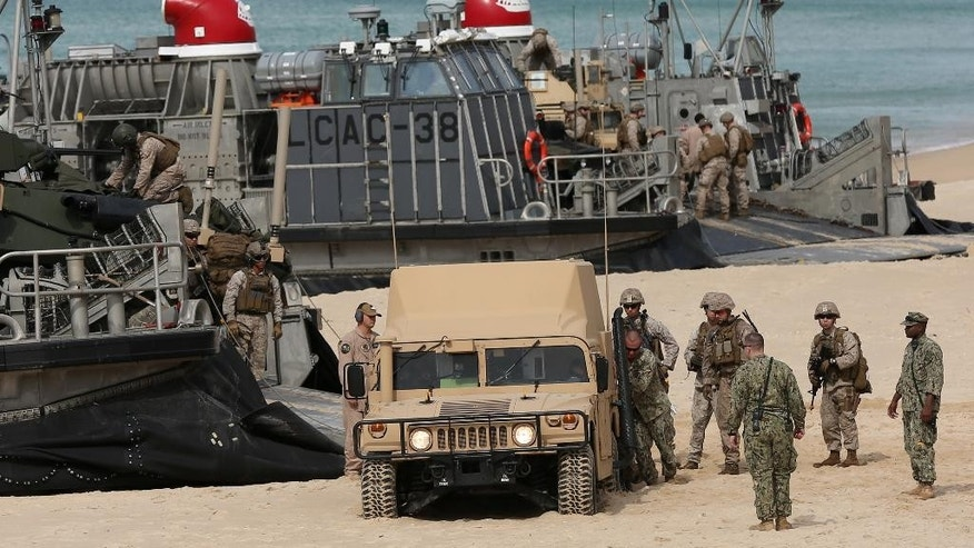 FILE - In this Oct. 20, 2015 file photo, U.S. Marines try to free an armored vehicle from the sand after it got stuck while getting off a U.S. Navy hovercraft while landing at the beach during the NATO Trident Juncture exercise 2015 at Raposa Media beach in Pinheiro da Cruz, south of Lisbon. NATO is putting on its most fearsome display of military might in over a decade, a choreographed exercise of soldiers, ships and planes, all meant to hone and test its current abilities. (AP Photo/Steven Governo, File)