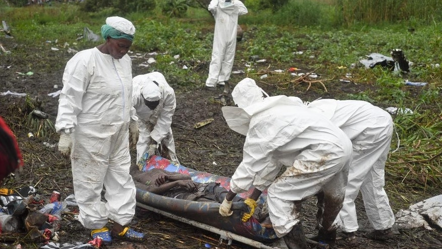Responders remove a body from the wreckage of a cargo plane which crashed in the capital Juba, South Sudan Wednesday, Nov. 4, 2015.  The cargo plane was taking off from the South Sudanese capital of Juba when it crashed along the banks of the Nile River, killing dozens according to witnesses and the government.  (AP Photo/Jason Patinkin)