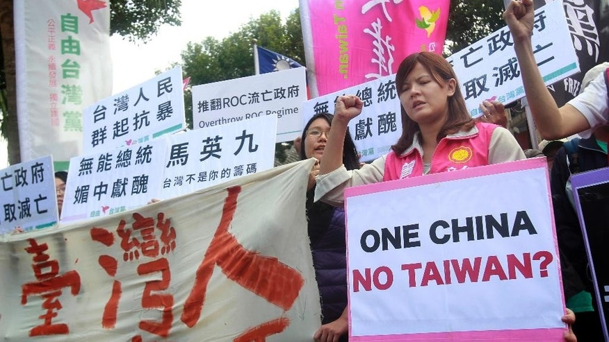 Opposition protesters shout slogans with placards opposing the planned meeting of Taiwan's President Ma Ying-jeou with his China counterpart Xi Jinping in Taipei, Taiwan, Wednesday, Nov. 4, 2015. Taiwan's President Ma and China President Xi will meet in Singapore, Saturday, Nov. 7, 2015, for the first time since civil war divided their lands 66 years ago, their governments said Wednesday, a highly symbolic move that reflects quickly improving relations between the formerly bitter Cold War foes. (AP Photo/Chiang Ying-ying)