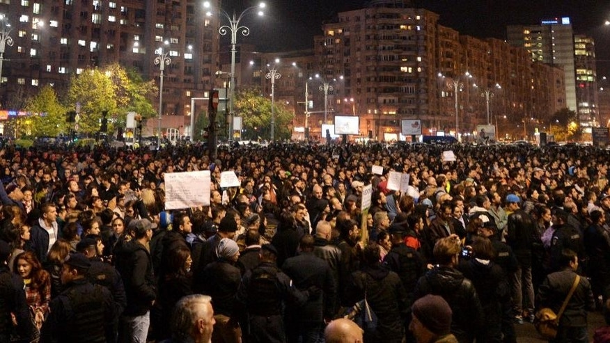 People stand in Victory square during protest in front of the government headquarters in Bucharest, Romania, Tuesday, Nov. 3, 2015. Up to eight thousand people joined a protest against the endemic corruption affecting all levels of the administration, calling for the resignation of the government.(Andreea Alexandru, Mediafax via AP) ROMANIA OUT