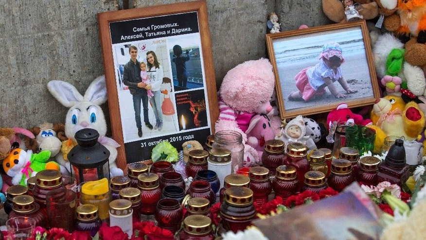 Pictures show young family of Alexei Gromov, 27, his wife Tatyana, 26, and their ten-month-old daughter Darina, who was the youngest passenger in Russia's deadliest plane crash last Saturday, which stole the lives of 224 people, struck Alexei's home town of Gatchina lie surrounded candles and toys at a monument of Soviet fighter aircraft MiG-21 in Gatchina, Russia, Wednesday, Nov. 4, 2015. These days residents of this small historical town, located 40 kilometers outside the center of St. Petersburg in Leningrad region and known for being home to one of major Russian imperial palaces, come to the local monument of Russia's first military air field featuring a Soviet fighter aircraft MiG-21.