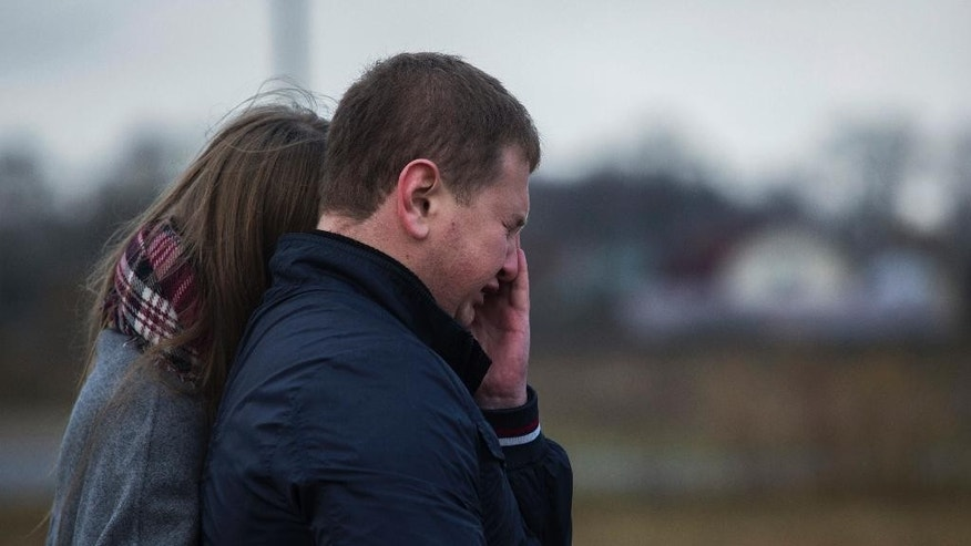 Andrey Dorokhin, right, cries as he and other Alexei Gromov's schoolmates come to pay their last respect to young family of Alexei Gromov, 27, his wife Tatyana, 26, and their ten-month-old daughter Darina, who was the youngest passenger in Russia's deadliest plane crash last Saturday, which stole the lives of 224 people, struck Alexei's home town of Gatchina at a monument of Soviet fighter aircraft MiG-21 in Gatchina, 40 kilometers (25 miles) outside St. Petersburg, Russia, Wednesday, Nov. 4, 2015. On Wednedsay, a group of about 15 young people, who were Alexey Gromov's classmates and friends, gathered in front of the monument. In the background of a gloomy November day they spoke quietly to each other, some young women and men cried. (AP Photo/Elena Ignatyeva)