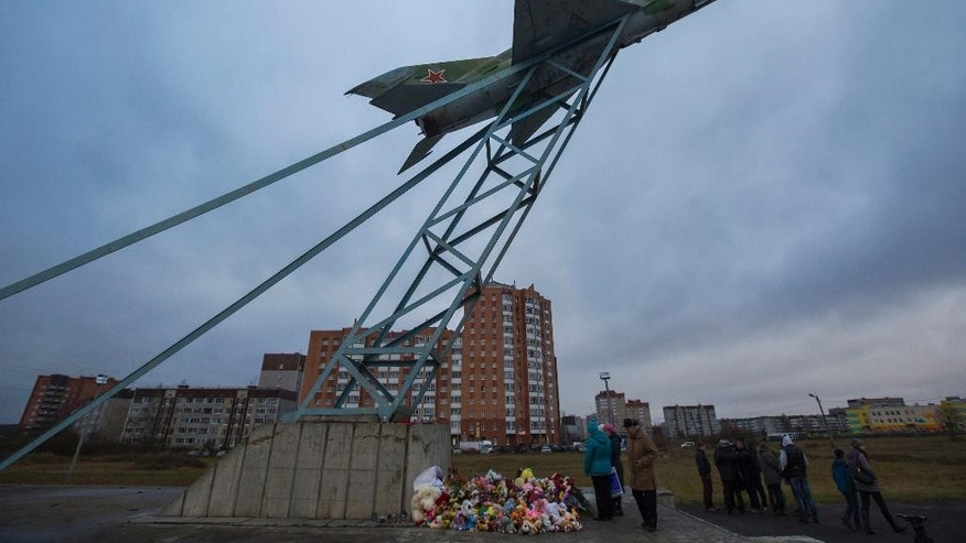 Local people come to pay their last respect to young family of Alexei Gromov, 27, his wife Tatyana, 26, and their ten-month-old daughter Darina, who was the youngest passenger in Russia's deadliest plane crash last Saturday, which stole the lives of 224 people, struck Alexei's home town of Gatchina at a monument of Soviet fighter aircraft MiG-21 in Gatchina, 40 kilometers (25 miles) outside St. Petersburg, Russia, Wednesday, Nov. 4, 2015. These days residents of this small historical town, located 40 kilometers outside the center of St. Petersburg in Leningrad region and known for being home to one of major Russian imperial palaces, come to the local monument of Russia's first military air field featuring a Soviet fighter aircraft MiG-21. (AP Photo/Elena Ignatyeva)