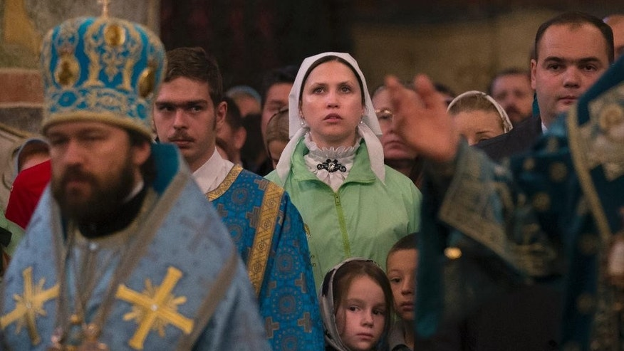 Orthodox believers attend a religious service marking the People's Unity Day inside the Cathedral of the Assumption at Cathedral Square in the Kremlin in Moscow, Russia, Wednesday, Nov. 4, 2015. The People's Unity Day is a public holiday in Russia. (AP Photo/Alexander Zemlianichenko)