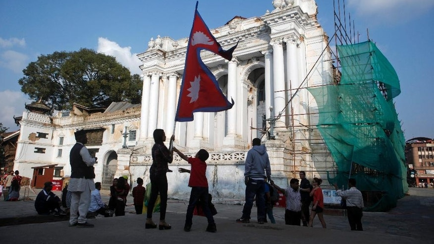 In this Oct. 24, 2015 photo, a Nepalese girl holds a Nepalese flag in front of a palace damaged in the April 25 earthquake at the Basantapur Durbar square in Kathmandu, Nepal. Aid groups are warning of a crisis unfolding in Nepal as winter approaches, especially for the many of the estimated 400,000 Nepalis who live at elevations of 1,500 meters (4,920 feet) or higher. Some are still living in temporary shelters in camps across the country, though there is no official number. Their tents and huts built with tin sheets protected them from the monsoon rain but will be little match for the snow and below-freezing temperatures expected in mountain villages by the end of November. (AP Photo/Niranjan Shrestha)
