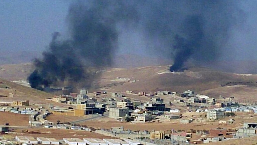 FILE - In this Saturday, Aug. 2, 2014, file photo, smoke billows from the Lebanese town of Arsal, a Sunni Muslim town near the Syrian border in eastern Lebanon. A bomb exploded in the Lebanese town of Arsal on Thursday, Nov. 5, 2015, killing and wounding several people including clerics who were holding a meeting at the time, security officials and state media said. (AP Photo, File)