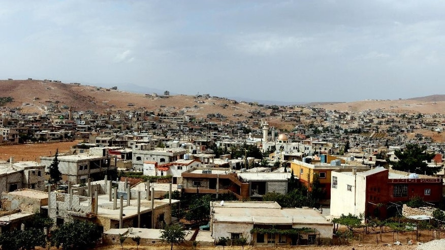 FILE - This Tuesday, Oct. 2, 2012 file photo shows a general view of Arsal, a Sunni Muslim town eastern Lebanon near the Syrian border. A bomb exploded in the Lebanese town of Arsal on Thursday, Nov. 5, 2015, killing and wounding several people including clerics who were holding a meeting at the time, security officials and state media said. (AP Photo/Bilal Hussein, File)