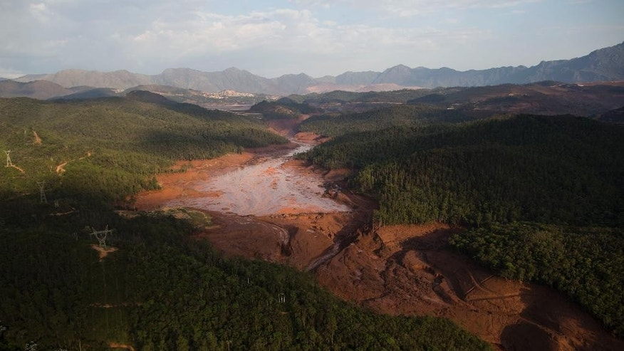 Aerial view of the small town of Bento Rodrigues after a dam burst on Thursday in Minas Gerais state, Brazil, Friday, Nov. 6, 2015. Brazilian rescuers searched feverishly Friday for possible survivors after two dams burst at an iron ore mine in a southeastern mountainous area.  (AP Photo/Felipe Dana)