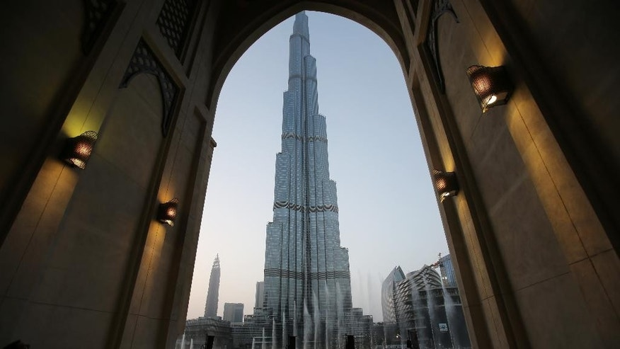 FILE - In this Monday, April 13, 2015, with the world tallest tower, Burj Khalifa, in the background, tourists and visitors watch and take photos of the Dubai Fountain in Dubai, United Arab Emirates. The Burj Khalifa announced Thursday, Nov. 5, it is selling tickets on the United Arab Emirates' weekend of Friday and Saturday for sunrise viewings. (AP Photo/Kamran Jebreili, File)