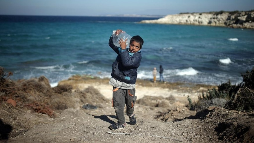 A boy carries a can of water near a beach from where migrants are traveling by dinghies to the Greek island of Chios from Turkish coast near Cesme, Izmir, Turkey, Wednesday, Nov. 4, 2015. More than 300,000 people have traveled on dinghies and boats from nearby Turkey to Greek islands this year, with dozens dying along the way.(AP Photo/Emre Tazegul)