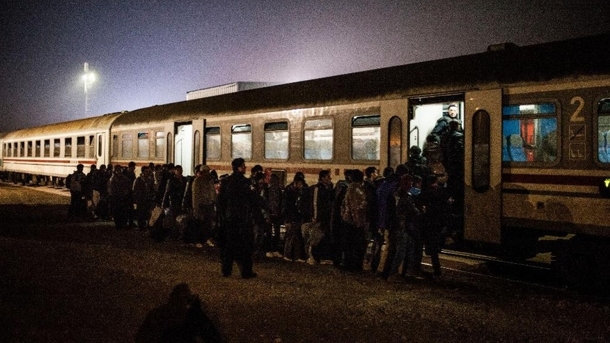 Migrants queue to board a train on the way to Slovenia at a makeshift train station within a temporary camp in Slavonski Brod, Croatia, Wednesday Nov. 4, 2015.  The weather is getting colder and many migrants are not equipped to cope with prolonged periods without shelter. (AP/Manu Brabo)